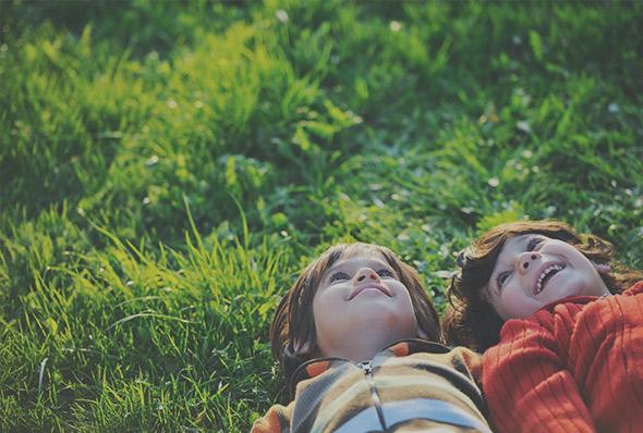 Siblings lying in the field
