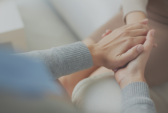 A psychiatrist in Brisbane holding hands with her patient with depression and anxiety problems.